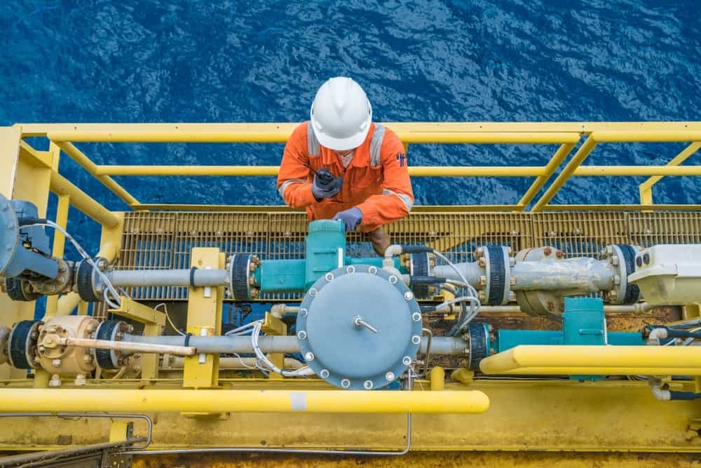 Barriers to communication : Oil and gas engineer on off-shore platform using radio for remote communication